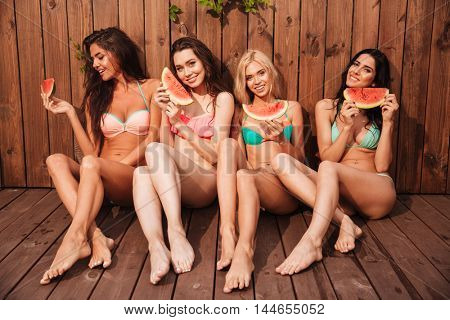Four young cute funny girls eating watermelon over wooden background
