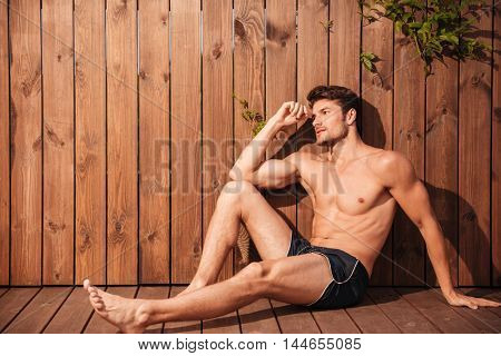 Handsome young pensive man sitting at the poolside and looking away over wooden background