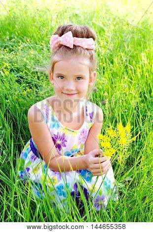 Adorable smiling little girl on the meadow with flowers in summer day outdoor