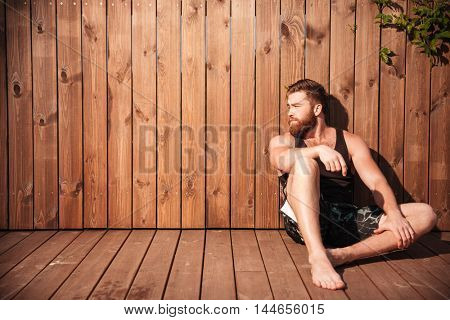 Handsome young bearded man sitting and looking away over wooden background