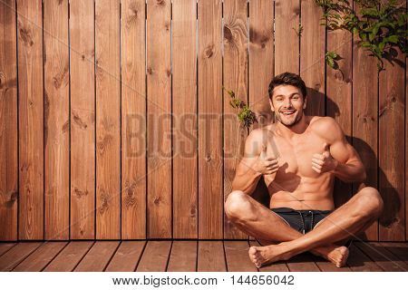 Handsome young happy man sitting and showing thumbs up over wooden background