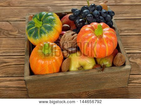 Autumn harvest in a wooden box on a brown background