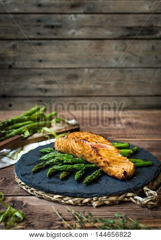 Pan seared salmon with asparagus over black stone plate