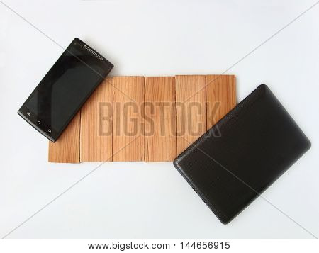 On a white background is a wooden texture and a phone with a tablet. There is a place for advertising text