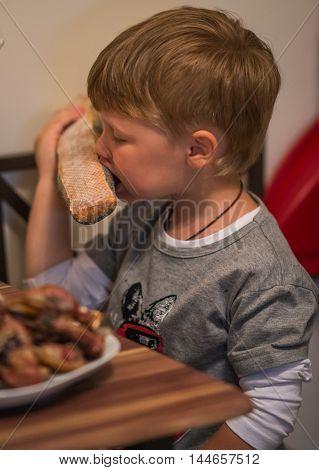 Little Boy Eating Long Loaf Bread In Kitchen