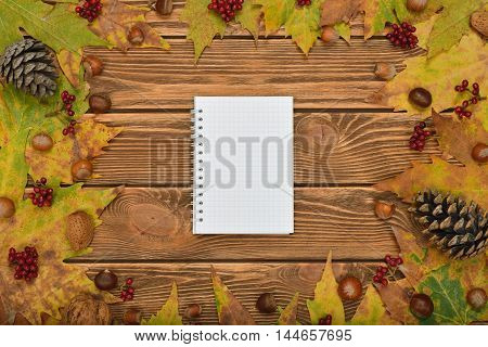 Autumn leaves and notebook on a brown background