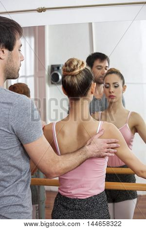 Trainer Assisting Female Ballet Dancer In Dance Studio