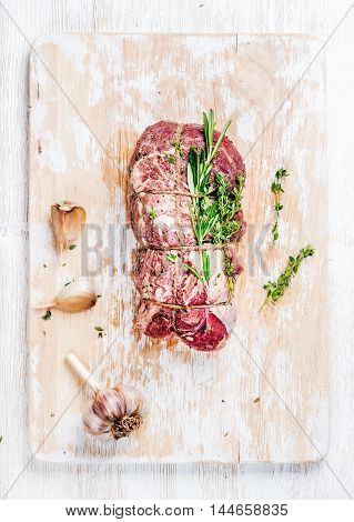 Raw uncooked roastbeef meat cut with rosemary, thyme and garlic on old white painted wooden background, top view, vertical composition