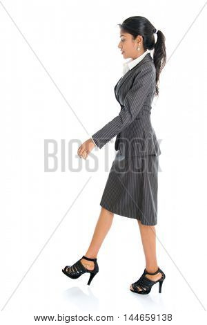 Full length side view of Indian businesswoman walking isolated on white background.