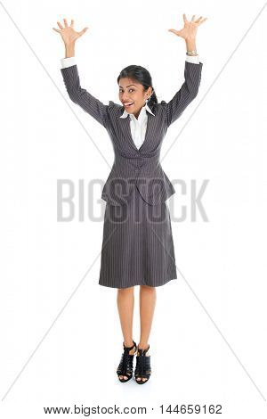 Full length portrait of excited Indian business woman arms raised, standing isolated on white background.