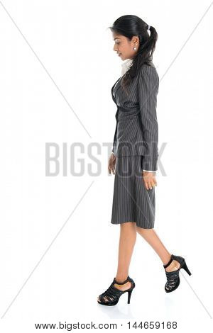 Full length side view of Indian business woman walking isolated on white background.