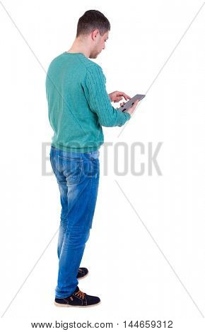 back view of business man uses mobile phone man in a green jacket and jeans standing cancer and working on plashnete.