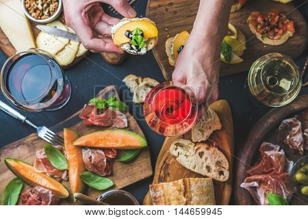 Italian wine antipasti snack variety and man's hands holding glass of rose wine and bruschetta, top view, selective focus