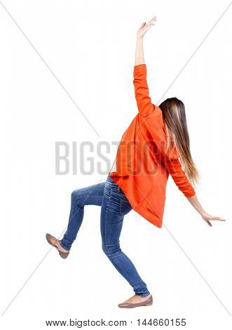 Balancing young woman. or dodge falling woman. girl in a red jacket, trying not to fall.