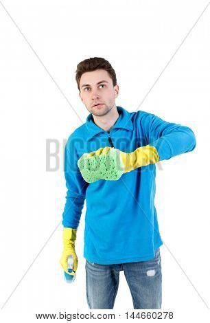 front view of a houseowner in gloves with sponge and detergent. man watching. curly-haired man in a blue jacket with warm green sponge cleans the glass.