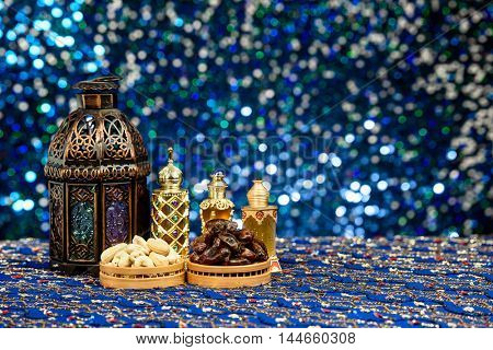 Eid and Ramadan theme background with dates and nuts with perfume bottles against a blue glitter background
