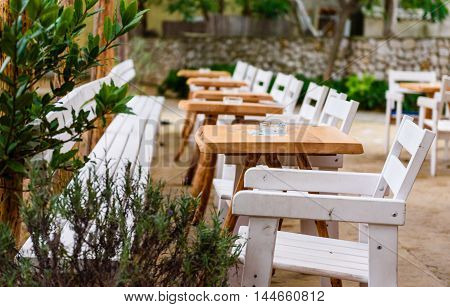 Caffe bar or restaurant with white chairs and tables. Nice place to eat or drink in nature with green trees and leafs.