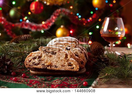 Traditional German Christmas cake Stollen with Marzipan, Berries Nuts, Cinnamon, Raising on a rustic wooden festive table. Holiday xmas celebration decorations.