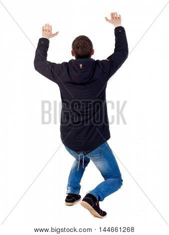 back view of business man protects hands from what is falling from above. Isolated over white background. Man in warm jacket sat down trying to holding something over his head.