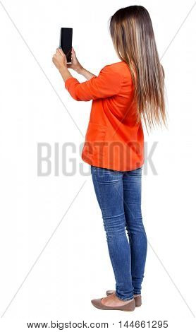back view of standing young beautiful woman using a mobile phone. girl in a red jacket holding vertically in front of the plate.