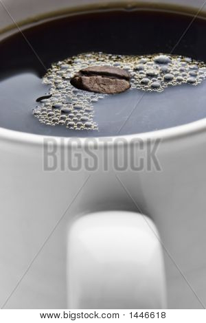 Cup Of Coffee With A Bean Floating In It