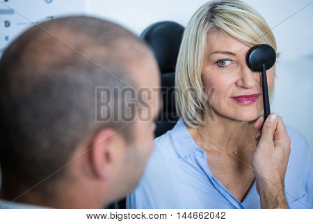 Optometrist examining female patient with medical equipment in ophthalmology clinic