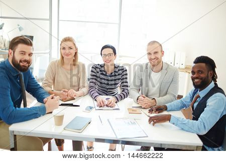 Group of businesspeople, men and women, pausing discussion to look and smile at camera during meeting in office