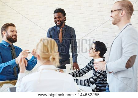 Group of young business men and women meeting in office, talking and telling stories and jokes at coffee break, African American man standing among them smiling brightly