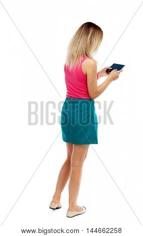back view of standing young beautiful woman using a mobile phone or tablet computer. Isolated over white background. Blonde in a red sweater and green skirt playing tablet.