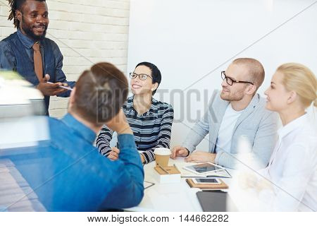 Group of executives at conference table in office listening intently to lively charismatic Afro-American colleague presenting idea to them