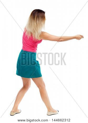 back view of standing girl pulling a rope from the top or cling to something. Isolated over white background. Blonde in a red sweater and green skirt clings to the rope.