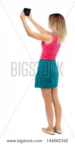 back view of standing young beautiful woman using a mobile phone. Isolated over white background. Blonde in a red sweater and green skirt photographing something in the sky on the tablet.