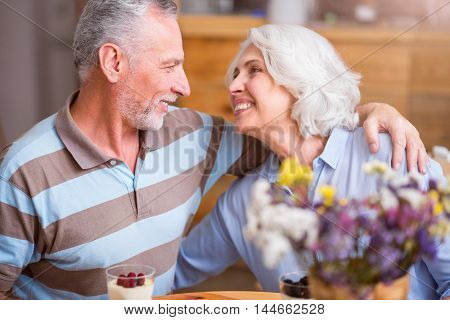 Warm heart. Cheerful delighted senior couple smiling and embracing while sitting at the table