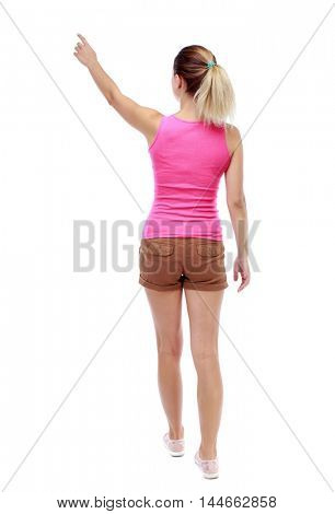 Back view of pointing woman. beautiful girl. Isolated over white background. Sport blond in brown shorts goes back frame showing thumb up.