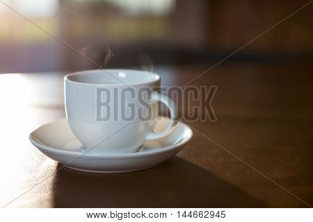 Close-up of coffee cup with saucer on a table in coffee shop