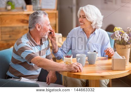 Love and care. Cheerful content senior loving couple sitting at the table while eating dessert together