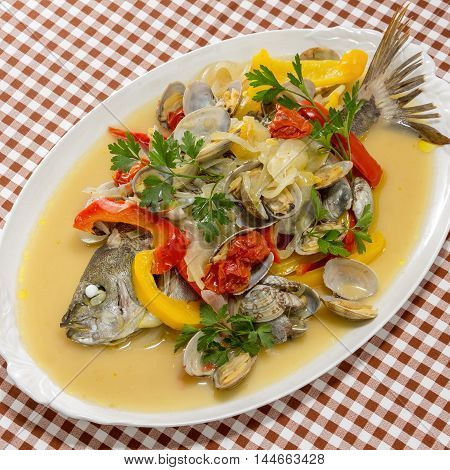 Steamed grouper fish with clams chili and herbs on white platter on caro table
