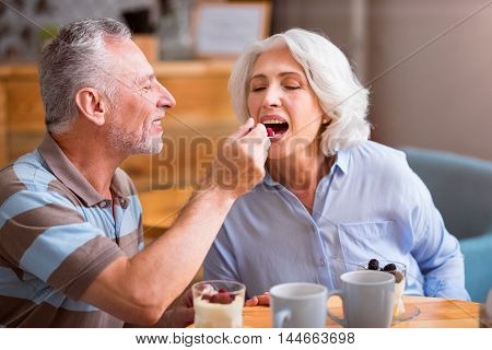 Help yourself. Cheerful senior loving couple smiling and eating dessert while sitting in the cafe