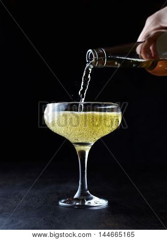 Pouring cider into a glasses standing on the bar table. Romantic evening. Black background, celebration time.