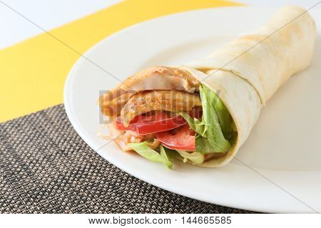 The kebab wrap roll with tomatoes and lettuce on white platter