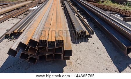 Metal rolling. Long steel square tubes folded on the ground