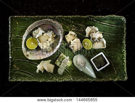 Abalone tempura with black sauce lemon and salt on wooden tray in black background