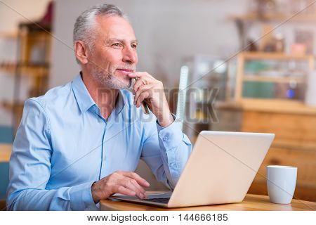 Mull it over. Thoughtful content senior man thinking and using laptop while sitting at the table
