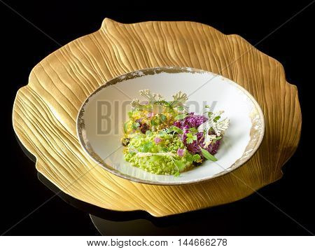 Cauliflower in symphony and vegetable caviar on art platter in black background