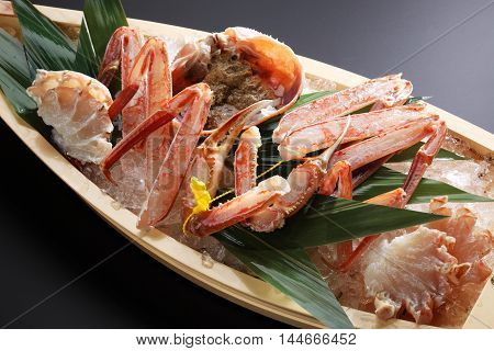 Red Echizen king crab legs with ice on wooden boat trayd