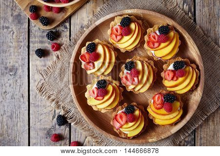 Tartlets with vanilla custard and fresh raspberries, blackberry and peach served on wooden tray with baking forms, kitchenware on the old wooden table. Top view. Dark rustic style.