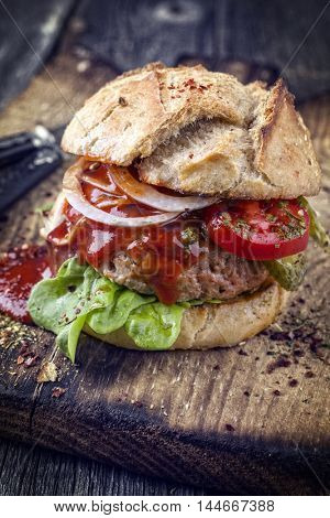 Barbecue Hamburger with Tomato and Lettuce Leaf on old Cutting Board