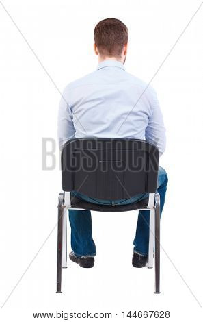 back view of business man sitting on chair. Bearded businessman in white shirt sits on a chair.