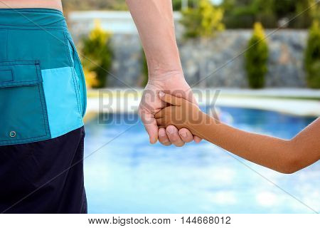 Swimming pool. Father holds the hand of a small child on a blue background
