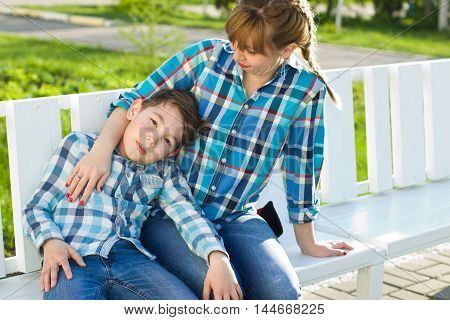 Mother and son on the bench in the park in spring